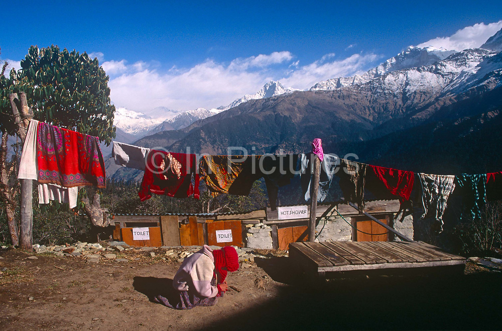 A child plays outside its home with the backdrop of snow-tipped Himalayan mountain peaks, a location also serving as a trekkers rest house with hot, solar-powered showers, on 10th November 1995, in Ghorepani, Himalayas, Nepal.