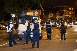© Licensed to London News Pictures. 10/07/2015. London, UK. Police officers investigating a crime scene on Lordship Lane in Wood Green, north London where a man has died and a woman has been taken to hospital following an apparent drive-by shooting on Friday, July 10, 2015. Photo credit: Tolga Akmen/LNP