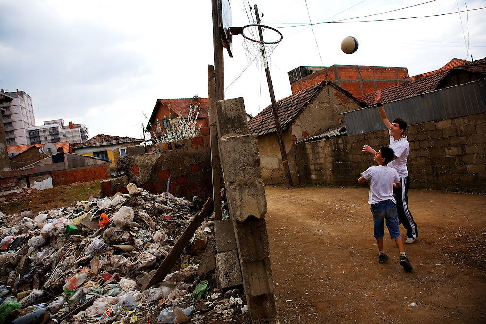"""""""Kosovo on the Edge"""" -- Albanian teenagers play a game of basketball in an impoverished section of Mitrovica, next to the remains of a burned out house which has been turned into a community garbage dump."""