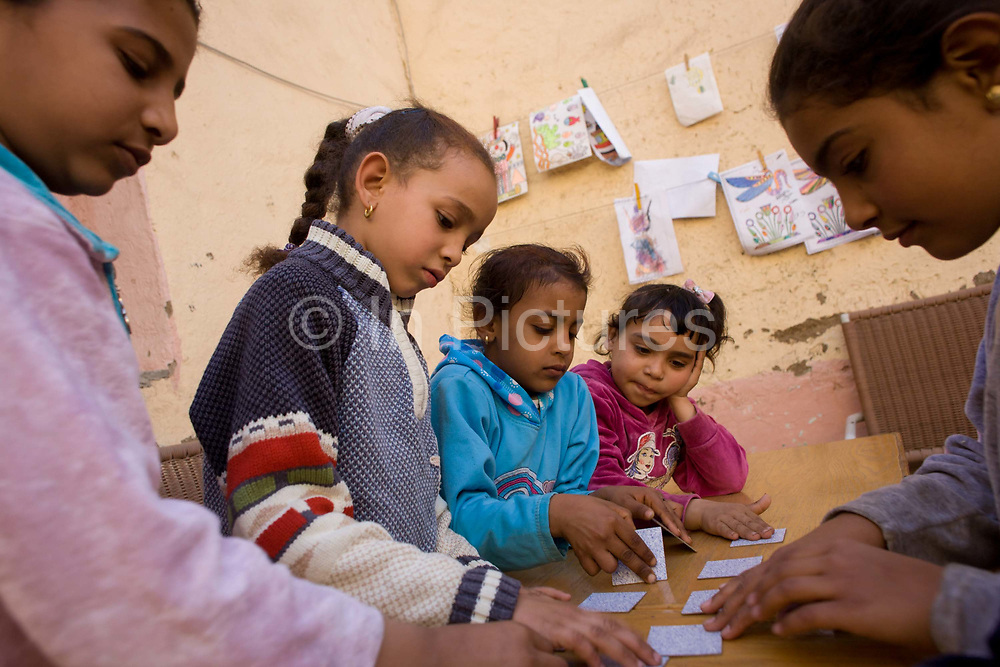 Local children play memory card games from a Belgian teaching volunteer at the American-sponsored Theban Mapping Project Library on the West Bank of Luxor, Nile Valley, Egypt. The Theban Mapping Project's goal is to enable local people to have a place where they can read and learn as state schools are under-resourced, lacking basic teaching aides such as books. The organisation is run by American Egyptologist Dr Kent Weeks who is committed to the original goal of accurately documenting the archaeological heritage of Thebes. (Photo by Richard Baker / In Pictures via Getty Image).