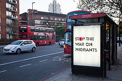 London, UK. 10 November, 2019. Remembrance Sunday artwork by Protest Stencil is displayed at a bus shelter in south London. The artwork contains the text 'Stop The War on Migrants', features a red poppy, references the government's hostile environment policies and calls for reflection on Britain's colonial past and present.