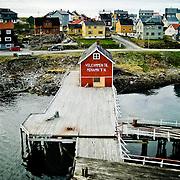 Three weeks aboard the Kong Harald. Hurtigruten, the Coastal Express. Small red house on a wharf.