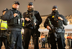 © Licensed to London News Pictures. 31/12/2018. London, UK. Armed police keep watch as crowds go through a security check on The Mall as they arrive to celebrate New Year's Eve in central London.  Over 100,000 people are attending London's ticketed fireworks display on the banks of the River Thames for New Year's Eve tonight. Photo credit: Peter Macdiarmid/LNP