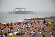 People on Brighton Beach on a misty summer day with the derelict West Pier looming behind. Destroyed by fire in 2003, there are plans for rejuvinating this iconic structure. Brighton, East Sussex.