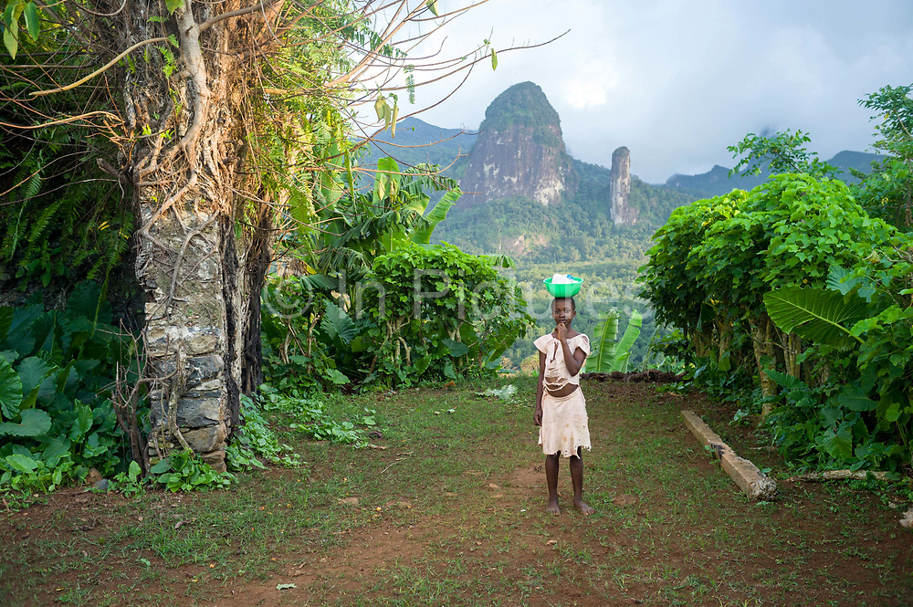 A child carrying a bowl on her head stands in from of the Pico de Príncipe L and the Pico Cão Grande, the two highest mountains on the island, Principe, Sao Tome and Principe<br /> Sao Tome and Principe, are two islands of volcanic origin lying off the coast of Africa. Settled by Portuguese convicts in the late 1400s and a centre for slaving, their independence movement culminated in a peaceful transition to self government from Portugal in 1975.