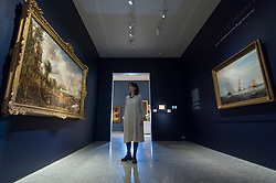 "© Licensed to London News Pictures. 11/01/2019. LONDON, UK. A staff member views ""The Opening of Waterloo Bridge ('Whitehall Stairs, June 18th, 1817')"" by John Constable (L) and ""Helvoetsluys"", 1832, by J.M.W. Turner (R) which are exhibited at The Royal Academy of Arts in Piccadilly for the first time since the artists clashed at the Summer Exhibition in 1832.  Turner allegedly added a small dab of red paint to his canvas, which he then converted into an image of a buoy floating in the sea. when he saw his painting next to Constable's.  The two works form ""He has been here and fired a gun"": Turner, Constable and the Royal Academy, on display from 12 January to 31 March 2019.  Photo credit: Stephen Chung/LNP"