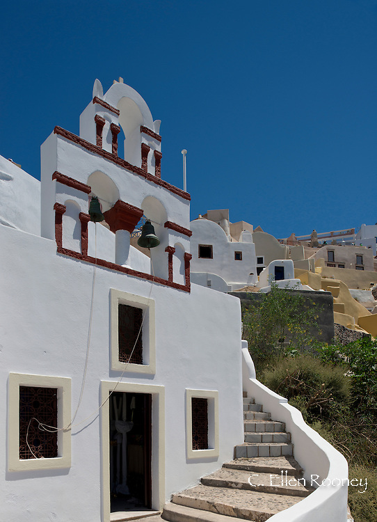 A colourful white washed church bell tower with red trim in Oia, Santorini, The Cyclades, The Aegean, The Greek Islands, Greece, Europe