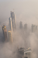 Aerial view of misty skyscrapers in Business Bay, Dubai, UAE.