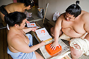 Takeuchi Masato (ring name Miyabiyama) makes a handprint during a break at pre-tournment practice in Nagoya,  Japan.  The prints are given to fans and sponsors. (Takeuchi Masato is featured in the book What I Eat, Around the World in 80 Diets.) MODEL RELEASED.