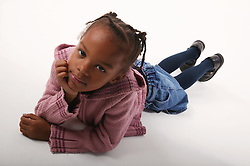 Young girl lying on the floor with hand under chin,