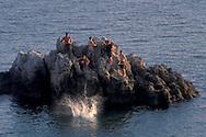 Young kids jumping of rock into calm sea water in harbor channel, Corona del Mar, Newport Beach, California
