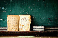 A tattered Third Grade spelling book sits on the dusty chalkboard ledge inside an abandoned school in Western NC.