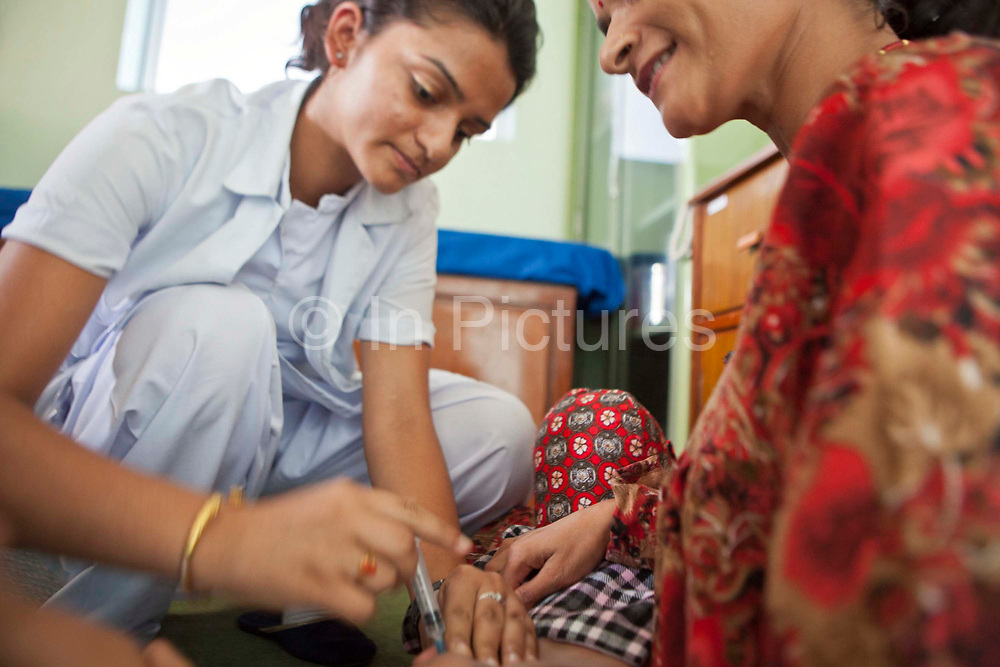 A Nepalese nurse gives a young child an injection on a feeding ward in the Friends of Needy Children Nutritional Rehabilitation Centre, Kathmandu, Nepal.  The patient's mother holds and reassures the child during the procedure.  The centre has recently been built to provide healthcare to malnourished children and education to mothers about nutrition and childcare.