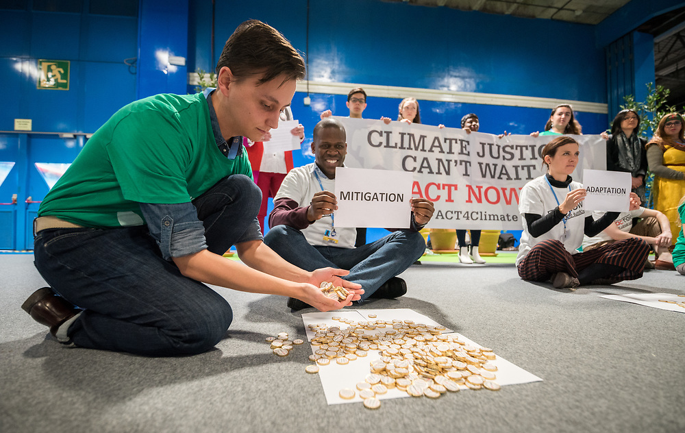 """11 December 2019, Madrid, Spain: ACT Alliance, Lutheran World Federation and World Council of Churches participants at COP25 illustrate the lack of balance in finance of the global climate response, where most of the finance is put into mitigation, some into adaptation, but very little into loss and damage, even though 'that's where the people are'. 'What do we want? Climate justice. When do we want it? Now!"""" they chanted. Here, Lutheran World Federation delegate Erik Bohm from Church of Sweden symbolically pours money into Mitigation."""