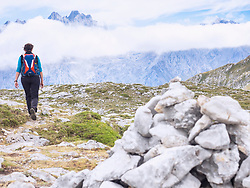 Woman on a hiking tour in the Picos de Europa near Covadonga, Asturias, Northern Spain. In background the summit of Picu Urriellu