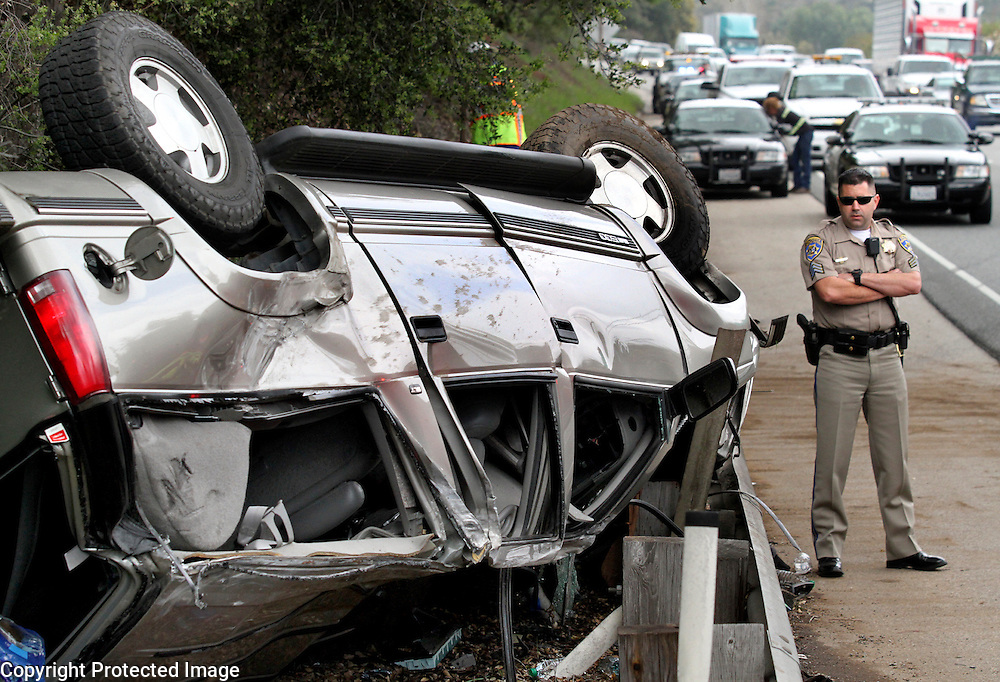 California Highway Patrol officer Grant Boles inspects a GMC SUV that rolled over on Highway 17 south of Mount Hermon Road in Scotts Valley, California. The driver and both passengers in the vehicle sustained injuries in the crash.<br /> Photo by Shmuel Thaler <br /> shmuel_thaler@yahoo.com www.shmuelthaler.com