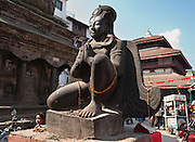 This massive stone winged Garuda statue kneels in front of Trailokya Mohan Narayan Temple (left), which is dedicated to Vishnu or Narayan, in Durbar Square (Palace Square, or officially called Hanuman Dhoka), Kathmandu, Nepal.