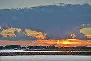 Nederland, Nijmegen, 18-7-2020 Binnenvaartschepen varen over de Waal, Rijn, langs de Ooijpolder bij een mooie, rode zonsonergang, ondergaande zon .. Een binnenvaartschip beladen met kolen, steenkool, vaart richting Ruhrgebied, Duitsland waar de kool gebruikt wordt als energiebron voor kolencentrales en hoogovens .. Foto: ANP/ Hollandse Hoogte/ Flip Franssen