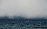 Snow falls down to lake level as seen from South Lake Tahoe, Calif., on Sunday, April 24, 2011.  (© 2011, Cindi Christie/Cyanpixel® Photography)