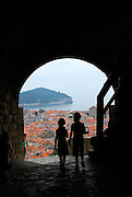 Two children (9 years old, 5 years old) silhouetted in archway of Minceta Tower, with Dubrovnik old town in background. Dubrovnik, Croatia.