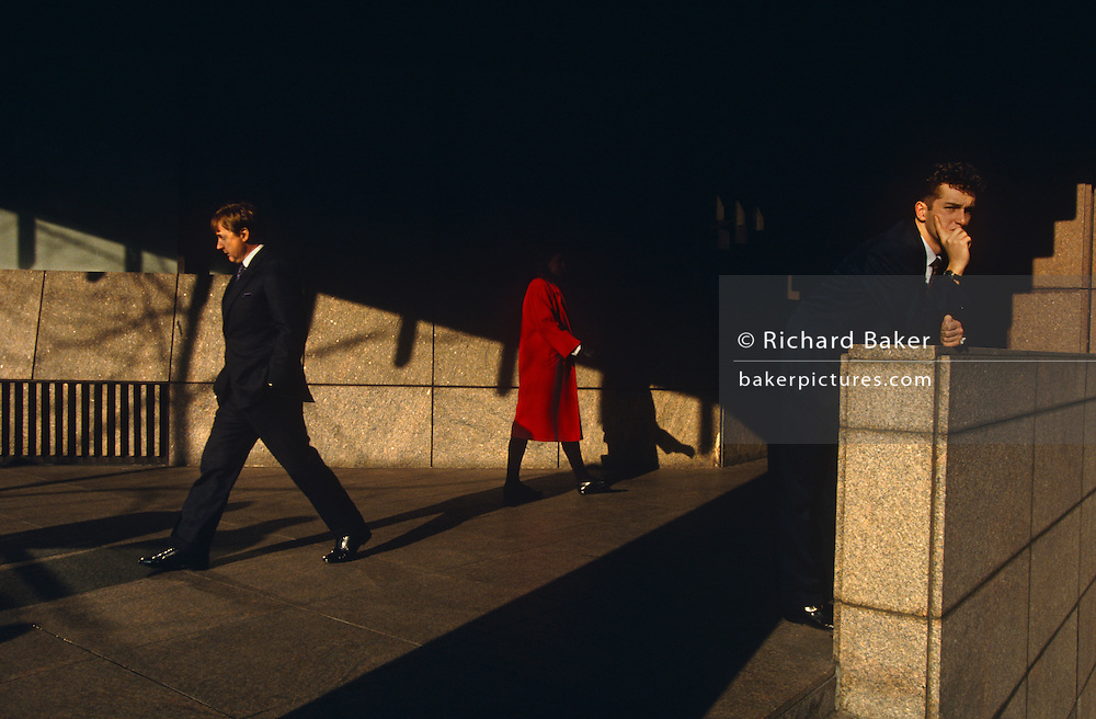 Striding across the picture in different directions, two office workers: A lady in a red coat whose head and identity is lost in shadow, and a man wearing a dark suit whose stride is purposeful and confident. A third person, another man, leans against a wall looking thoughtfully into the distance. There is more shadow than highlight in this scene taken at Broadgate, a private estate of financial institutions and global businesses in the heart of the City of London. There are no spring leaves on the trees whose shadows are falling on an opposite wall. The headless lady looks sinister minus her face and there is tension in this image of linear and diagonal space. The City of London has a resident population of under 10,000 but a daily working population of 311,000. The City of London is a geographically-small City within Greater London, England. The City as it is known, is the historic core of London from which, along with Westminster, the modern conurbation grew. The City's boundaries have remained constant since the Middle Ages but  it is now only a tiny part of Greater London. The City of London is a major financial centre, often referred to as just the City or as the Square Mile, as it is approximately one square mile (2.6 km) in area. London Bridge's history stretches back to the first crossing over Roman Londinium, close to this site and subsequent wooden and stone bridges have helped modern London become a financial success.