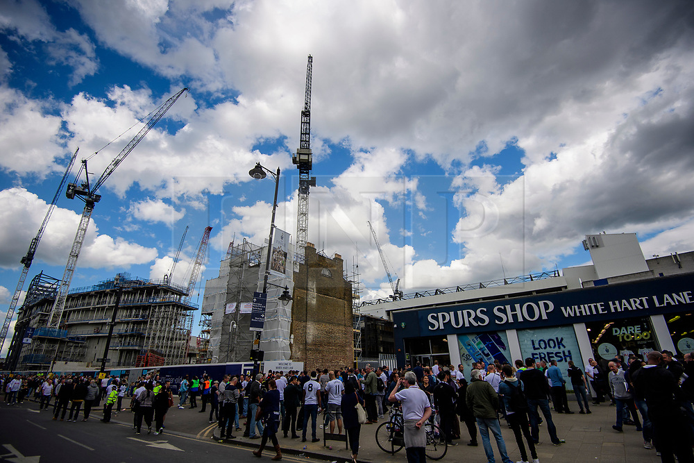 © Licensed to London News Pictures. 14/05/2017. London, UK. Fans  walk past the building site of a new stadium (left), next to White Heart Lane (right), in North London where Tottenham Hotspur F.C. are playing their final game at the ground, against Manchester united today (Sun). Known as 'The Lane', Tottenham have been playing at the ground for 118 years, but will be playing at Wembley next season while a new 60,000 seat stadium is built for the start of the 2018/19 season.  Photo credit: Ben Cawthra/LNP