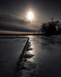 Moody image of the Lake Nokomis ice rink in January.  A child and parent are out on the ice behind the rink