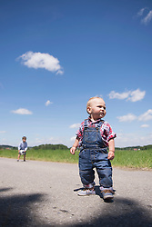Small baby standing on road with his brother playing football in the background, Bavaria, Germany