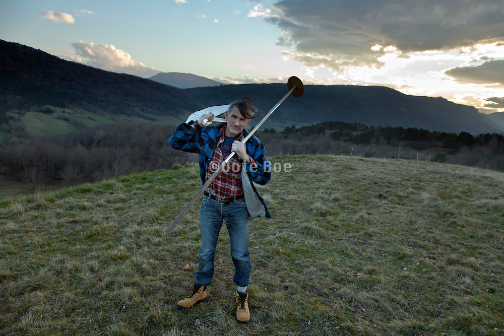 man holding a bag and pole standing in a field with mountain range in the background South France