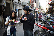 A young couple eat pizza outside a pizza shop in Khan Market, New Delhi<br /> Khan Market It is one of the most expensive retail streets anywhere in the world frequented mostly by the rich and foreigners