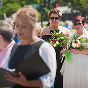 Liberty Manos, center and partner, Shannon Glatz, both of Akron, Ohio, listen as Officiant, Tiffany Newman, left, marries twenty-five gay couples in front of the Supreme Court of the United States, on June 21, 2013.  The couples traveled to Washington on the C-Bus of Love to get married en masse the week before decisions are expected to be made on the Defense of Marriage Act (DOMA) and Proposition 8. John Boal Photography.
