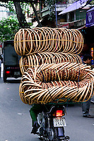 A motorbike cruises along the street with a mountain of cane baskets piled up on the back.