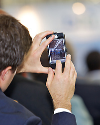 An audience member takes a photo as Blu Homes opened their West Coast factory on Mare Island in Vallejo, California Dec. 1, 2011.  Over 400 guests attended a ribbon cutting ceremony at the 250,000-square-foot facility.