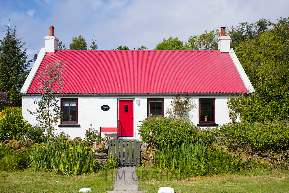 Quaint traditional whitewashed cottage with bright red front door and corrugated iron roof in Kilberry, Argyll and Bute, Scotland