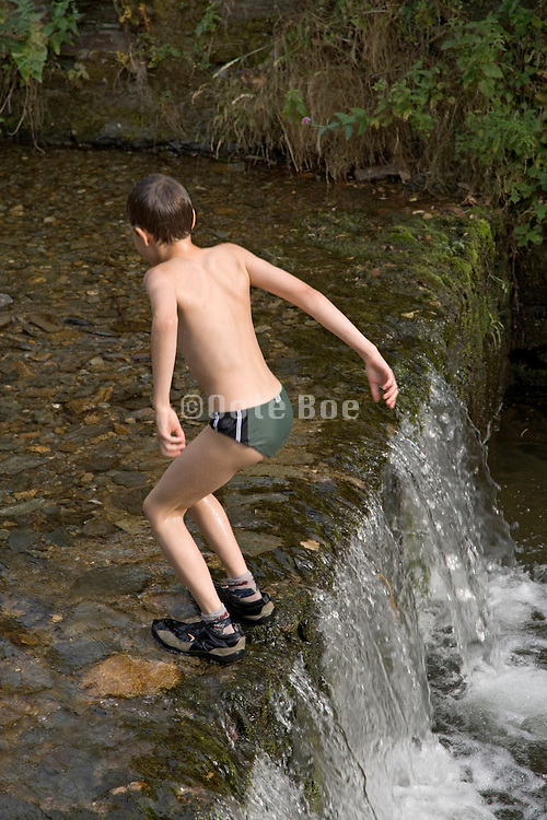 boy playing in a small river jumping backwards