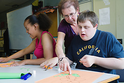 Teacher helping students with learning disabilities in art class,