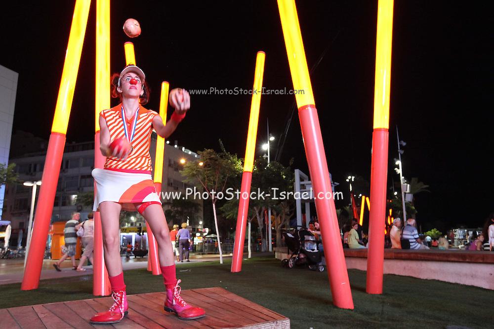 Open-air circus Clown juggles balls outdoors