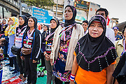 """15 JANUARY 2014 - BANGKOK, THAILAND: Thai Muslim women sing the Thai national anthem at the main stage for Shutdown Bangkok. Wednesday morning prayers were led by Buddhist monks, Muslim imams and a Catholic priest. Tens of thousands of Thai anti-government protestors continued to block the streets of Bangkok Wednesday to shut down the Thai capitol. The protest, """"Shutdown Bangkok,"""" is expected to last at least a week. Shutdown Bangkok is organized by People's Democratic Reform Committee (PRDC). It's a continuation of protests that started in early November. There have been shootings almost every night at different protests sites around Bangkok. The malls in Bangkok are still open but many other businesses are closed and mass transit is swamped with both protestors and people who had to use mass transit because the roads were blocked.    PHOTO BY JACK KURTZ"""