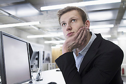 Young businessman thinking and working till late night in office, Freiburg im Breisgau, Baden-Wuerttemberg, Germany