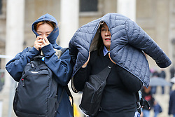 © Licensed to London News Pictures. 07/10/2019. London, UK. Members of public shelter from rain underneath jackets on a wet and windy afternoon in Trafalgar Square. Photo credit: Dinendra Haria/LNP