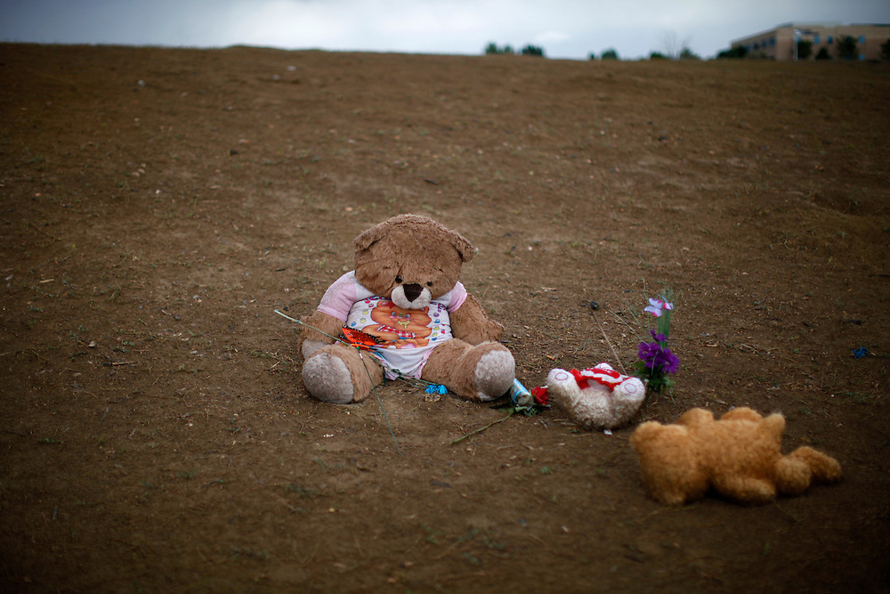 """Teddy bears lie in the mud at a memorial to the theater-goers killed in the mass shooting July 20, 2012 in Aurora, Colorado July 27, 2012. The third funeral in as many days took place Friday in this Denver suburb for victims of last week's deadly shooting rampage at a midnight screening of the latest """"Batman"""" film. REUTERS/Rick Wilking (UNITED STATES)"""