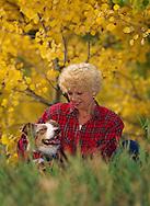 Woman with Australian Shepherd dog in fall foliage<br /> MODEL RELEASED, PROPERTY RELEASED