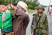 """Sept 26, 2009 -- PATTANI, THAILAND:  A Muslim man feeds his child as they pass a Thai soldier during a security operation near Krue Se Mosque in Pattani, Thailand, Sept. 26. Thailand's three southern most provinces; Yala, Pattani and Narathiwat are often called """"restive"""" and a decades long Muslim insurgency has gained traction recently. Nearly 4,000 people have been killed since 2004. The three southern provinces are under emergency control and there are more than 60,000 Thai military, police and paramilitary militia forces trying to keep the peace battling insurgents who favor car bombs and assassination.   Photo by Jack Kurtz / ZUMA Press"""