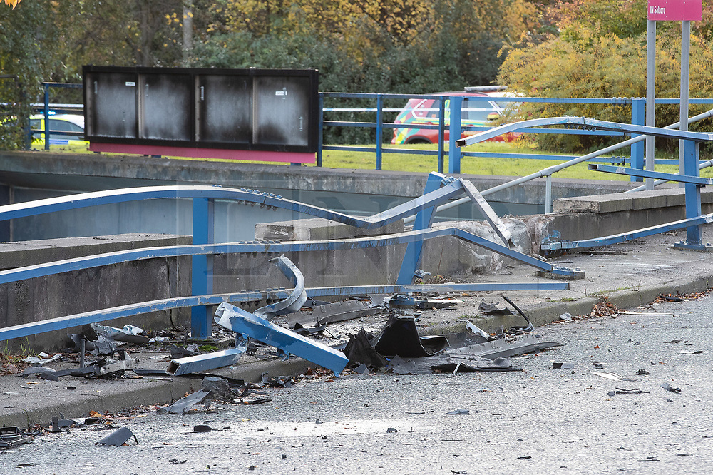 © Licensed to London News Pictures. 27/10/2019. Salford, UK. Smashed crash barrier , through which the car was driven . A car lies on its side on a pedestrian walkway at the Pendleton Roundabout on Broad Street in Salford . Members of the public pulled a man and a woman from the wreckage after a BMW car crashed through a barrier and landed on a pedestrian walkway below . Their condition is unknown and police , paramedics and fire crews are at the scene . Photo credit: Joel Goodman/LNP