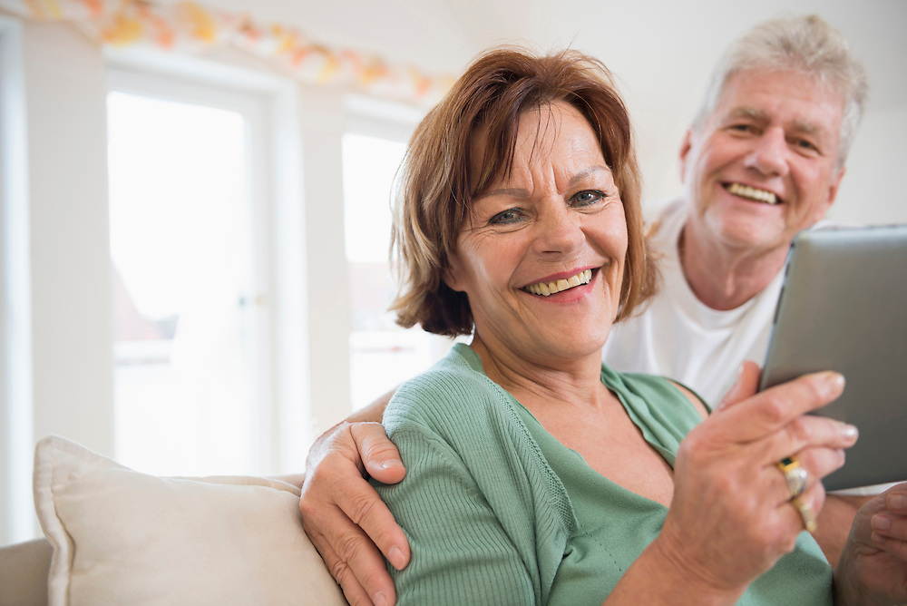 Portrait of senior couple with digital tablet, smiling