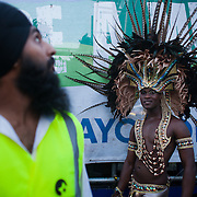 One of the last parades of the year. A young black wears a big feather head gear and a sikh security man looks up.  The Notting Hill Carnival has been running since 1966 and is every year attended by up to a million people. The carnival is a mix of amazing dance parades and street parties with a distinct Caribbean feel.