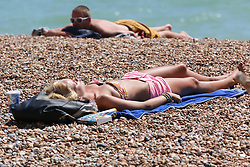 © Licensed to London News Pictures. 15/07/2014. Brighton, UK. People relaxing and sunbathing on Brighton beach at lunchtime. Temperatures in parts of the south east are expected to hit 30 degrees this week. Photo credit : Hugo Michiels/LNP