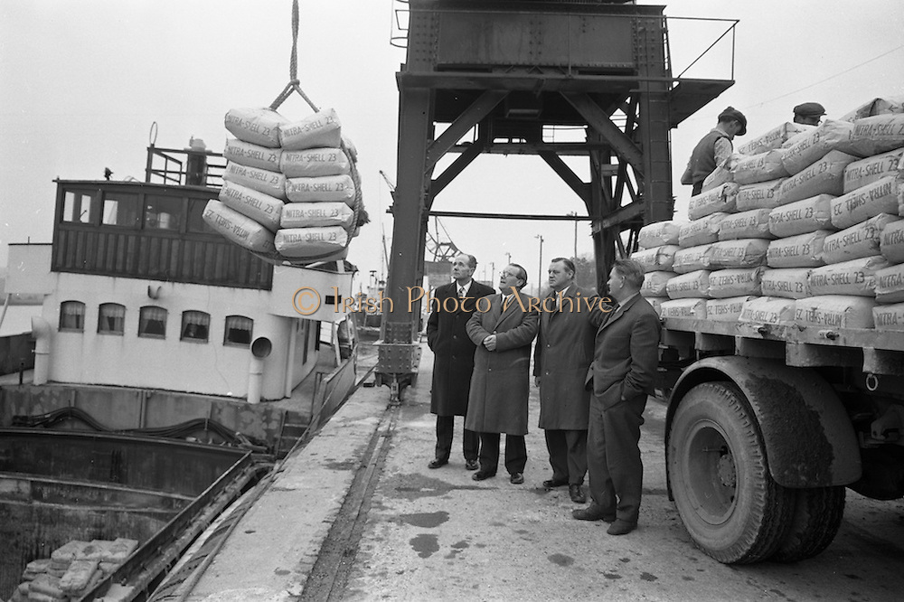 """11/02/1963<br /> 02/11/1963<br /> 11 February 1963<br /> Nitra-Shell 23 cargo discharged at New Ross, Co. Wexford. The """"M.V. Roelf Buisman"""" from Rotterdam on it's first visit to New Ross delivering 500 ton of Nitra -Shell 23 the first consignment of 23% Nitrogen imported into Ireland. Messrs. Albatross Windmill Fertiliser Co. Ltd. were the importers. Picture shows, looking at some of the Nitra-Shell 23 (l-r): Mr. M. Murphy, Manager J.J. Stafford (New Ross);   Mr. J.J. Boyle, General Manager of Shell and Albatross (Agricultural) Ltd.; Mr. E.F. Storey, Managing Director, Albatross Windmill Fertiliser Co. Ltd. and Captain  Smith of the """"Roelf Buisman""""."""
