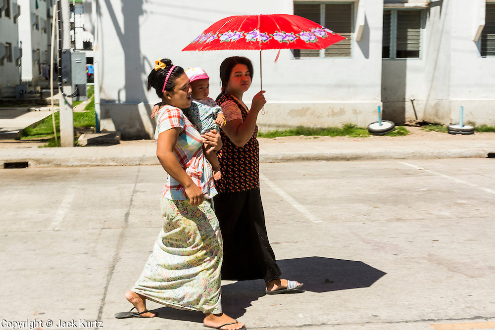 30 APRIL 2013 - MAHACHAI, SAMUT SAKHON, THAILAND: Burmese women walk through a housing complex that is home to almost 10,000 Burmese migrants in Mahachai. The Thai fishing industry is heavily reliant on Burmese and Cambodian migrants. Burmese migrants crew many of the fishing boats that sail out of Samut Sakhon and staff many of the fish processing plants in Samut Sakhon, about 45 miles south of Bangkok. Migrants pay as much $700 (US) each to be smuggled from the Burmese border to Samut Sakhon for jobs that pay less than $5.00 (US) per day. There have also been reports that some Burmese workers are abused and held in slavery like conditions in the Thai fishing industry.         PHOTO BY JACK KURTZ