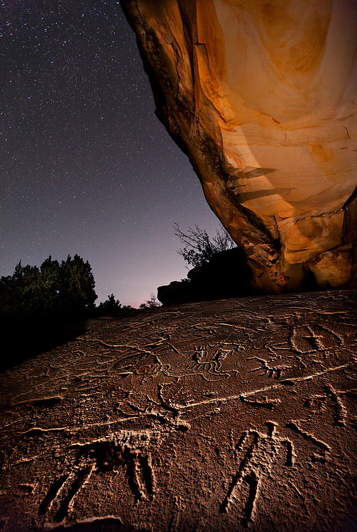 Ancient rock art adorns this sandstone slab in the canyon country of Western Colorado. It is speculated that some of the figures are Shoshone (Ute) and that some may be from the Fremont culture or even older.<br /> <br /> These illustrations are actually barely visible in direct light. But by placing my headlamp directly onto the rock and skimming light horizontally across the surface, I was able to bring the topography to life. Your mind might perceive the figures to be raised if you think the light is coming from the right. Only when you know that the light source is coming from the left can your mind correctly perceive that the images are etched into the stone. Moonlight illuminated the canyon wall.